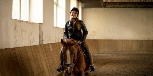 Tjej som rider på häst inomhus.