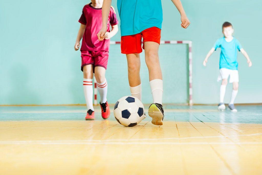 Barn som spelar fotboll inomhus.