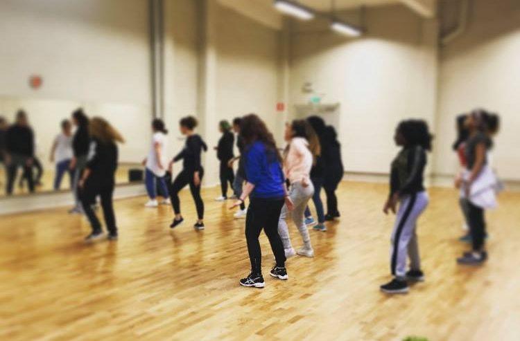 Personer som står i en danssal med speglar på väggen