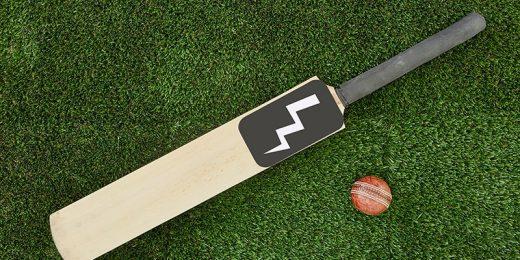 Ett cricketracket och en boll på en gräsmatta