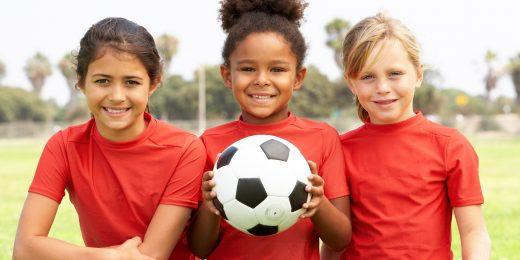 Tre tjejer på en fotbollsplan med en boll.