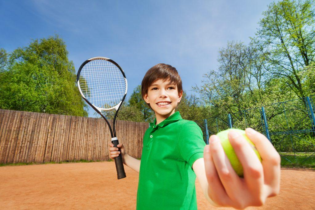 Kille som spelar tennis.