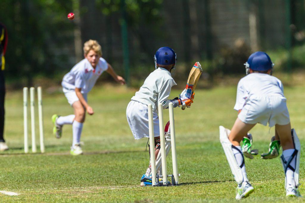 Killar som spelar cricket.