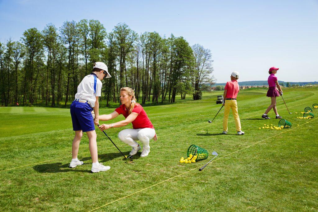 Ledare som visar barn hur de ska spela golf.