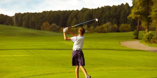 Kille som spelar golf.