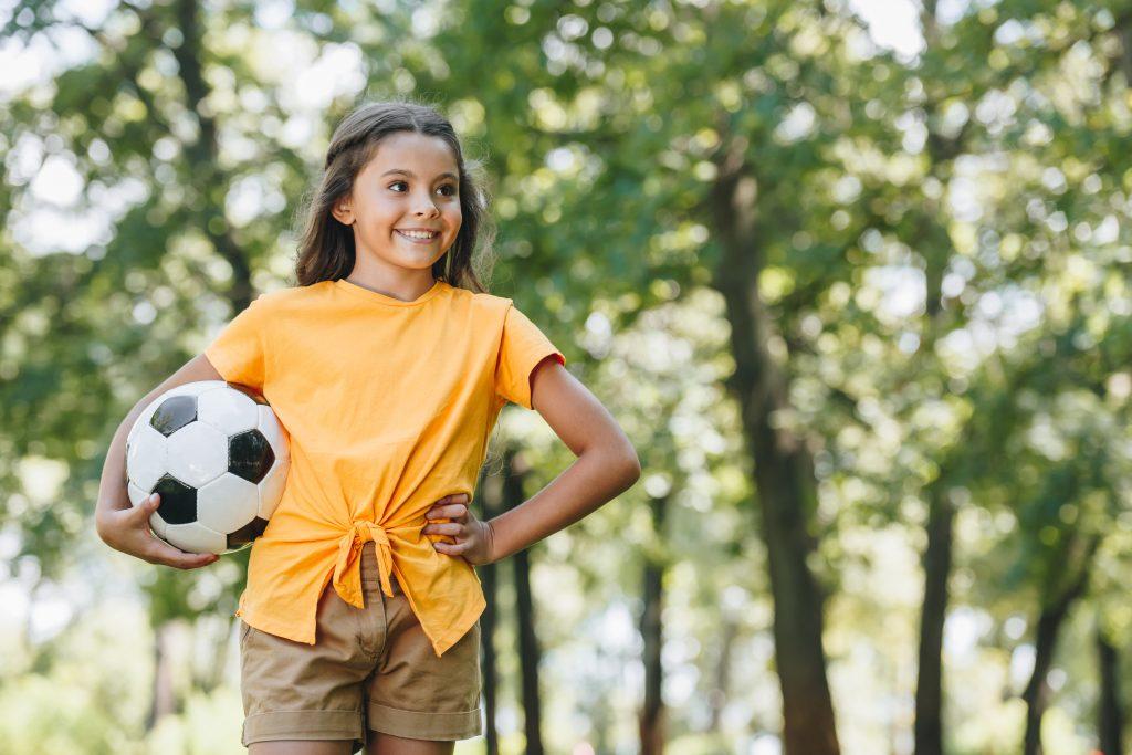 Tjej som står med en fotboll utomhus.