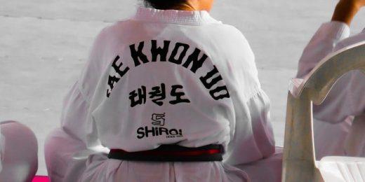 Tjej som sitter i ta0ekwondolokal med vit taekwondo-dräkt på sig.