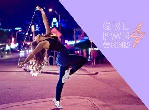 En tjej som dansar på en upplyst gata med en stad i bakgrunden