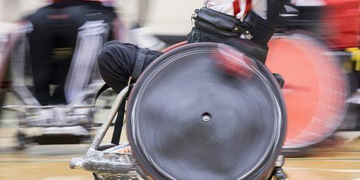 Personer i rullstol i idrottshall.