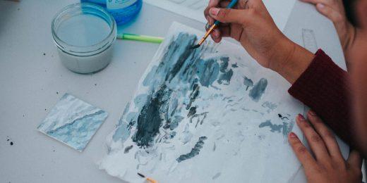 Ett barn målar med pensel på ett papper.