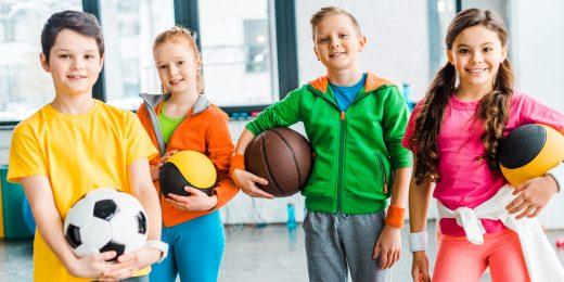 Barn som är klädda i träningskläder och håller olika bollar.