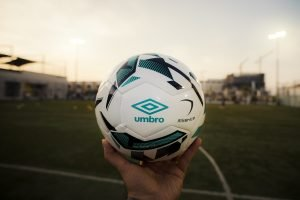 En person som håller upp en fotboll mot en fotbollsplan utomhus.
