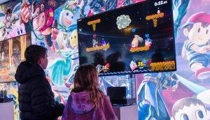 Två barn som står framför en TV-skärm och spelar TV spel