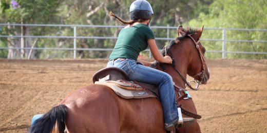 Tjej som rider på en häst.