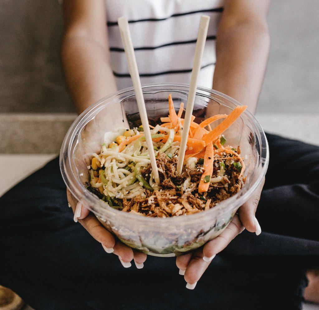 Tjej håller fram en asiatisk maträtt