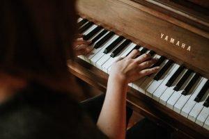 Tjej som spelar på ett piano.