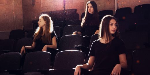 teater. tre tjejer i publiken.