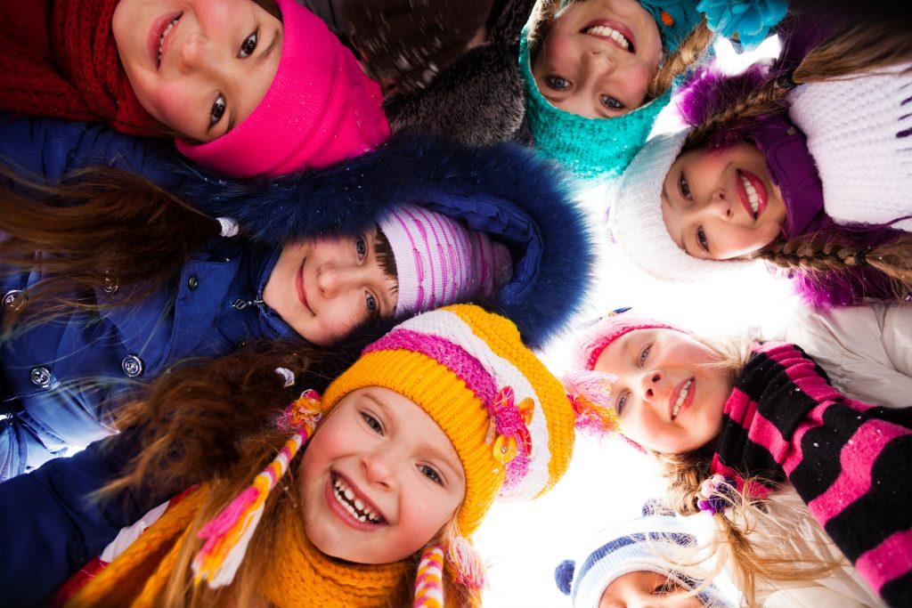 Lyckliga barn med vinterkläder.