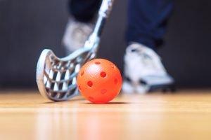 En innebandyklubba och en innebandyboll på golvet