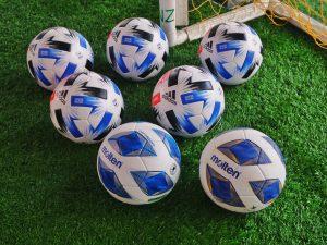 Flera fotbollar på konstgräsplan.