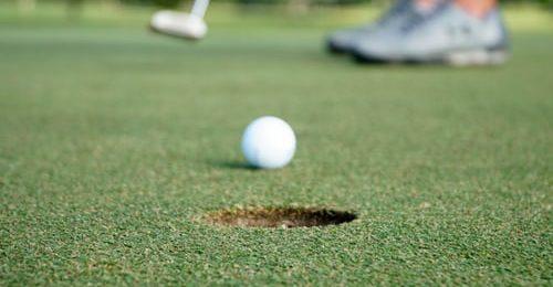 En golfboll som ligger på en grön golfbana.