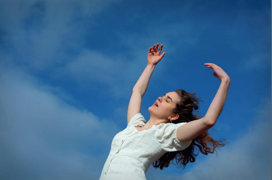 En tjej som dansar och håller upp armarna mot en blå himmel