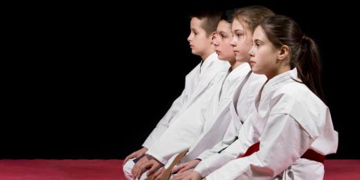 Barn som sitter i taekwondo dräkter.