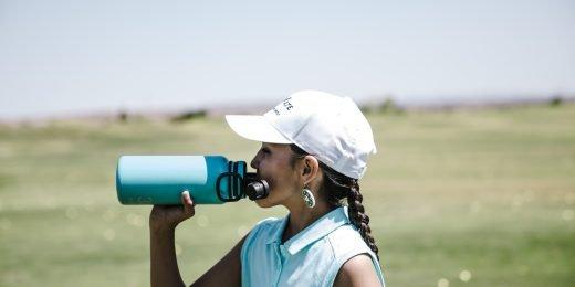 Tjej som dricker vatten ute på golfbanan.