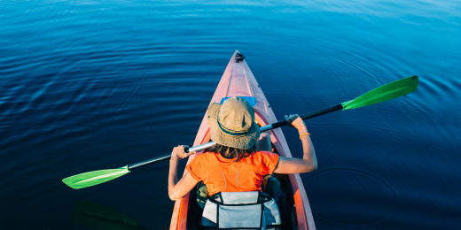 Person som paddlar kanot på stilla vatten