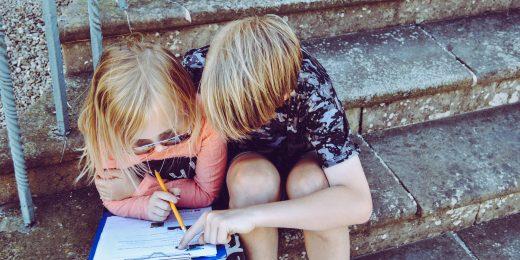 Barn som gör ett quiz utomhus på en trappa.