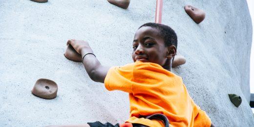 Kille som klättrar på en klättervägg.