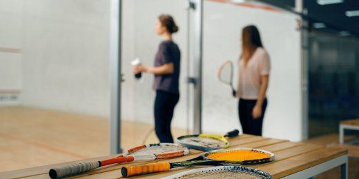 Två tjejer som är påväg att börja spela squash.
