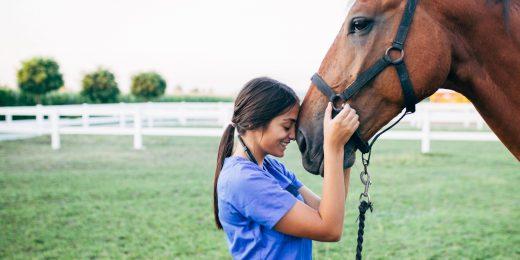 Tjej som står tillsammans med en häst.