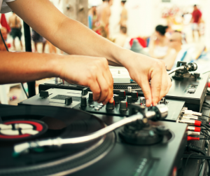 Person som står vid DJ-utrustning och spelar musik utomhus