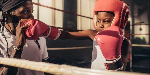 Barn som över på att boxas med ledare.
