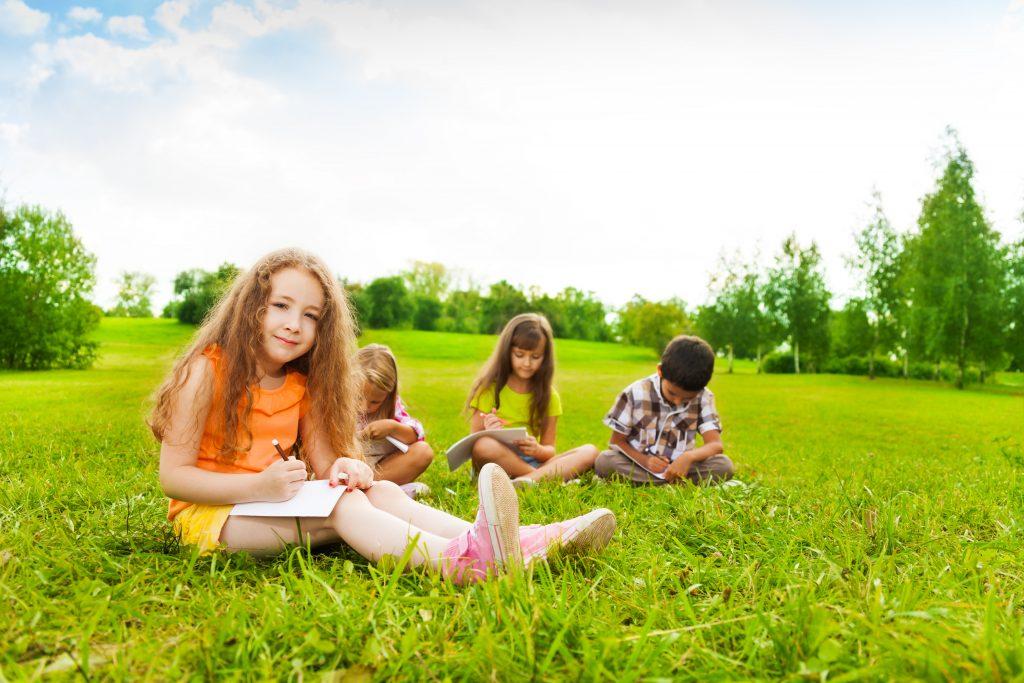Barn som sitter ute i gräset och läser.