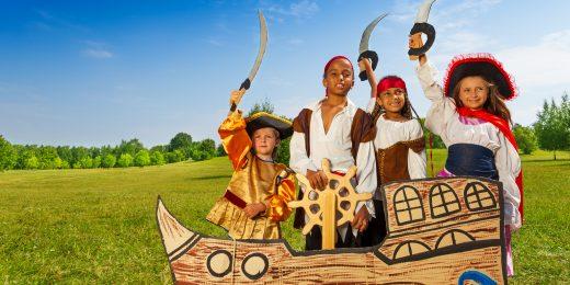 Barn utklädda till pirater med svärd och hattar bakom en båtkuliss på en gräsmatta