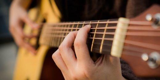 Person som spelar gitarr.