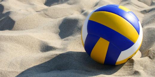 En blå, gul och vit volleyboll-boll i sanden