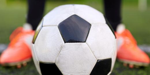 Grön gräsmatta med en person med fotbollsskor som står vid en fotboll. Det är inzoomat på personens skor och bollen.