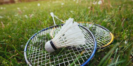 Badmintonrack på gräsmatta med en badmintonboll