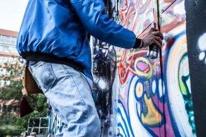 Kille som målar graffiti.