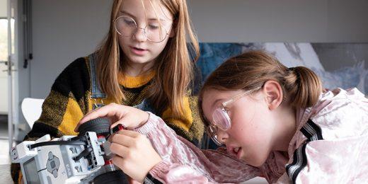 Två tjejer som sitter och bygger på en robot.