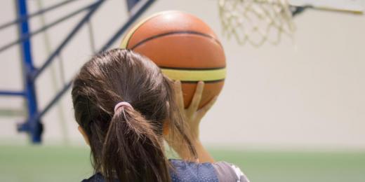 Tjej som håller i basketboll och ska kasta den i en basketkorg