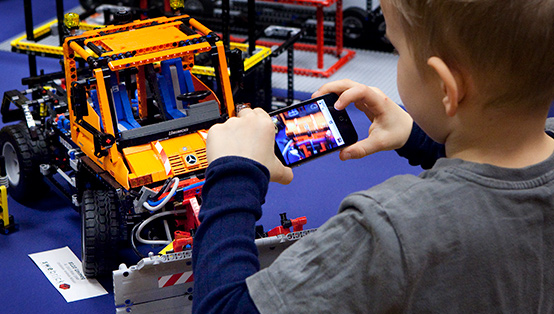 En pojke som tar en bild på en robotbil.