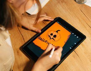 Person som ritar en halloweenpumpa med orange bakgrund på en ipad.