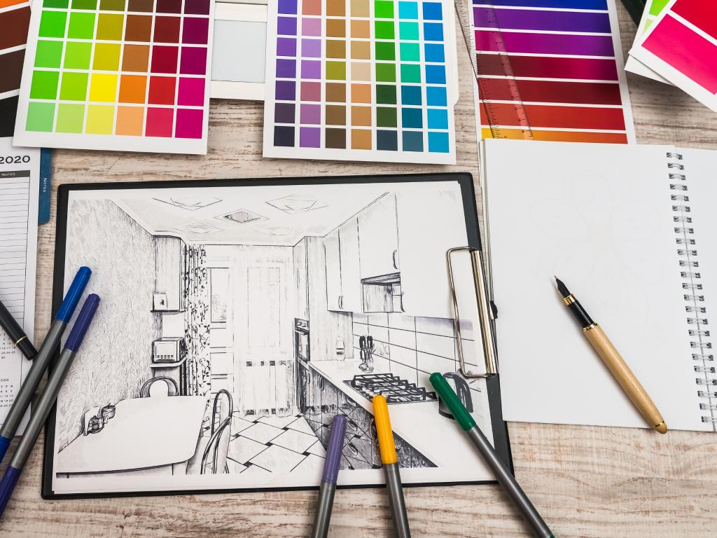 Ett bord fyllt med pennor, papper och färgkartor. På bordet ligger en skiss med en ritning av ett kök