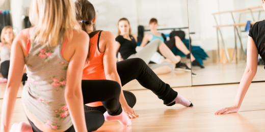 Personer som dansar och gör en rörelse sittande på ett golv i en sal med speglar