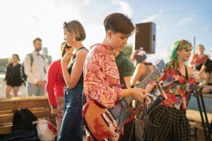 Barn och ungdomar som spelar instrument utomhus.