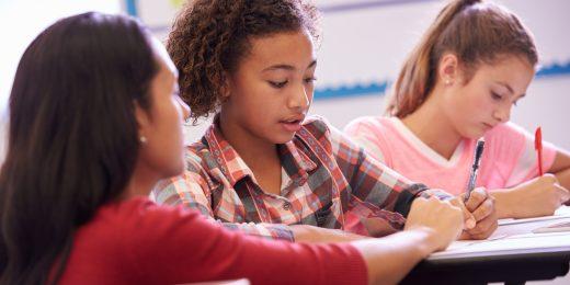 Två tjejer som sitter och skriver och en kvinnlig lärare hjälper till.
